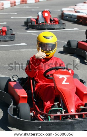 A smiling young  racer shows ok. Go-carting