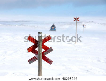 A snowmobile behind a red wooden signpost on a winter day in northern Sweden