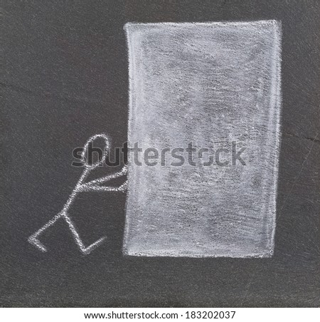 A stick figure pushing a big white block, drawn with chalk on a plate of slate.