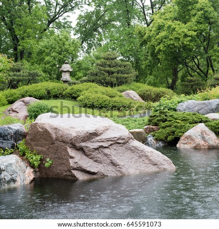 a stone bridge crosses a pond in a japanese garden