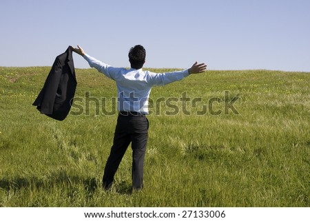 A successful business man with his arm outstretched on a green field