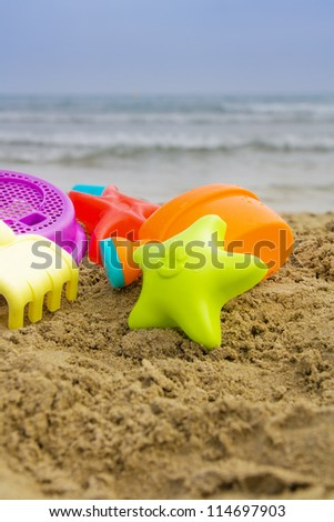 A summer beach scene with a starfish and beach toys