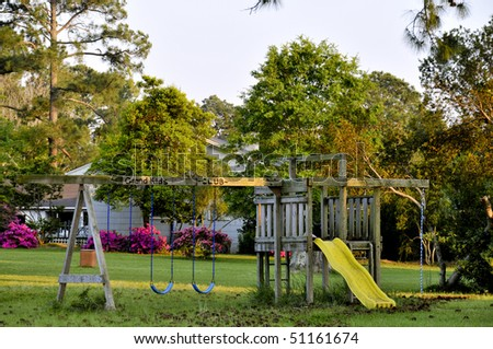 A swingset in the back of a yard