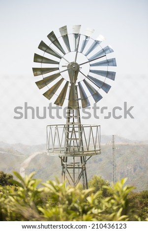 A tall windmill in a sunny day with some trees