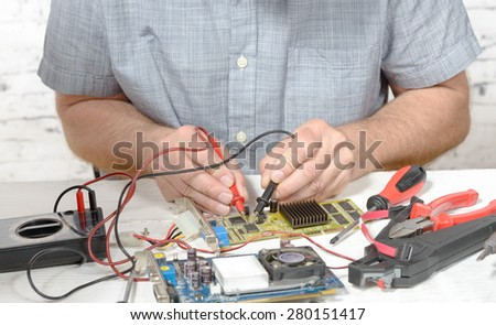 a technician repairing a computer with different tools