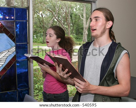 a teen boy and girl singing hymns in church.