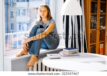 A teenage girl sits on window sill instead of reading books on the table