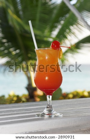 a tequila sunrise waiting to be drunk with a de-focused palm tree in the background, taken in Barbados