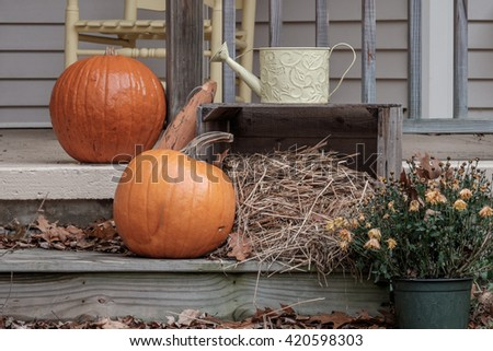 A Thanksgiving Holiday decorated porch with pumpkins and hay
