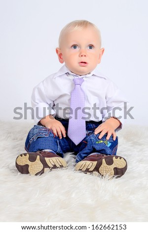 A toddler boy sitting on the floor in a white short, a purple tie and blue jeans surprised look in studio white background