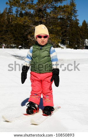 A toddler girl learns cross-country skiing at Lake Tahoe ski resort in Sierra Nevada mountains, California.