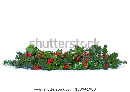 A traditional Christmas garland made from fresh holly with red berries, green ivy leaves and sprigs of conifer spruce. Isolated on a white background.