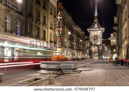 A tram rushes through the streets of Bern old town with the Zytgolgge tower in the background in Switzerland capital city at night.