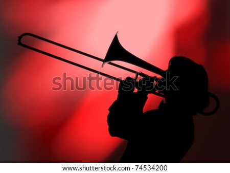 A trombone player plays his trombone in silhouette against a colorful background.