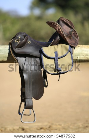 A vertical photograph of horse riding tack, including saddle, bag and leather hat