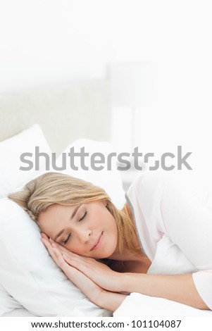 A vertical style shot with a woman resting, her head and hands both on the pillow.