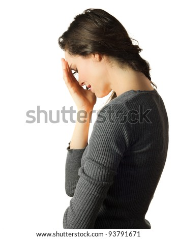 A very sad and depressed woman crying and hiding her face in her hands