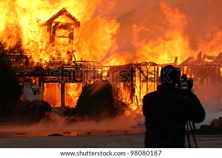 A videographer braving heat of a blazing fire that devoured what once was a two story wood framed building makes for a dramatic photograph.