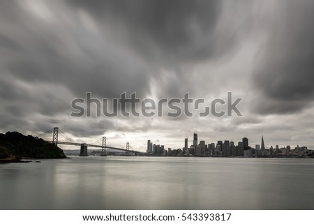 A view from Treasure Island Bay Bridge and San Francisco downtown mid cloudy day with long exposure cloud blur.