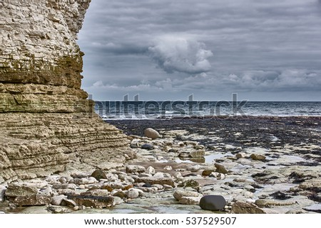 A view of the beach and surrounding rock at the North Landing at Flamborough Head on the north Yorkshire coast.