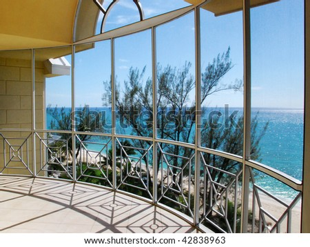 A view of the ocean through an glass window arch of a balcony.