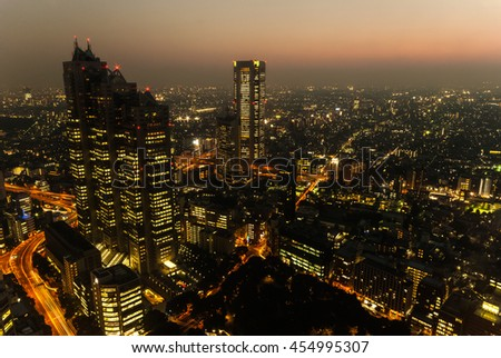 A view of the Tokyo skyline at dusk with the Shinjuku district and light trails in the foreground