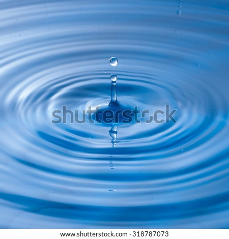 a water drop impact with water surface, causing rings on the surface.