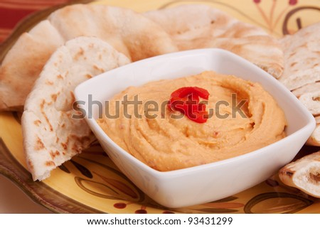 A white dish with red pepper hummus. Pita bread in the background.
