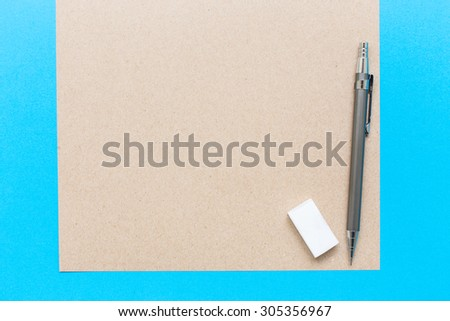 A white note book with lots of room for your text or image and a regular pencil and rubber on a wooden desk.