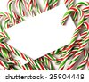 A white note-card, greeting card, or invitation surrounded by brightly color Christmas Candy Canes with copy space - stock photo