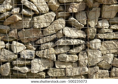 A whole page of a wall of dry caged stone background texture