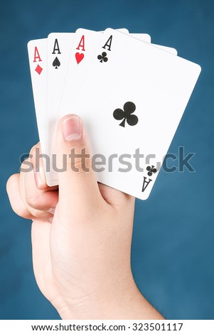 A winning poker in hand of four aces playing cards suits on blue chalkboard
