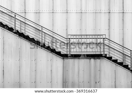 A wire stairway on the outside of a building with corrugated siding.