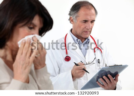 A woman blowing her nose at the doctor.