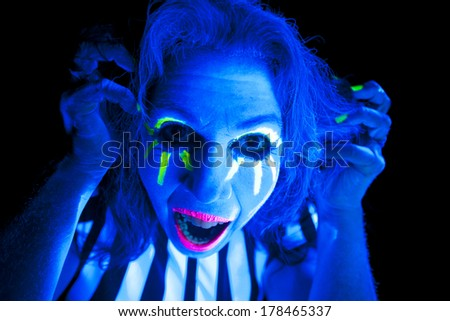A woman glowing in the ultraviolet light with a crazy expression.
