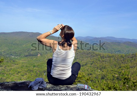 A woman hiker on an overlook looking for birds.