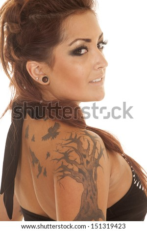 A woman in a black tank top with a tattoo of a tree and birds.