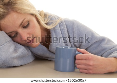 A woman in a blue robe sleepy with a mug.