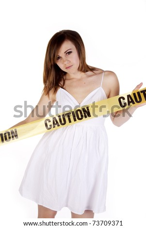 A woman in a white dress has caution tape in front of her.