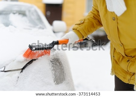 A woman in winter removes snow with the car