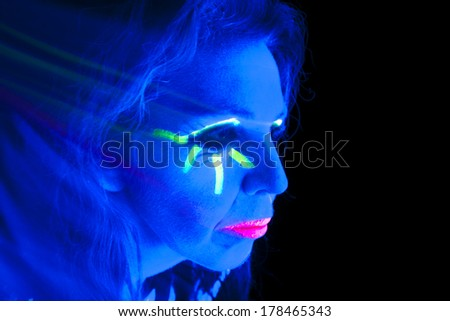 A woman is lit up with a black light looking to the side.