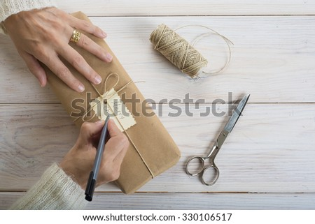 A woman is preparing gifts and writing labels for Christmas