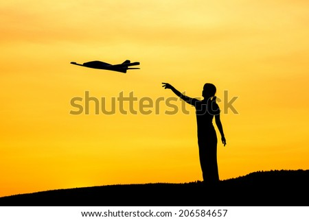 A woman launches a toy airplane during a sunset.