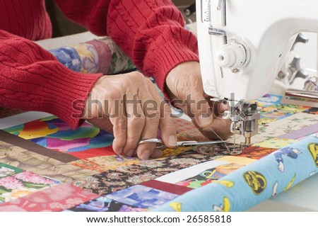 A woman quilter is cutting excess thread on a sewing machine.