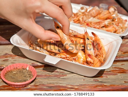 A woman's hand takes the ready-to-eat shrimp