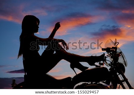 A woman sitting on her motorcycle with her heels on the tank of the bike