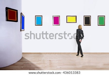 A woman standing with her back and looking at blank of one color frames in art gallery.