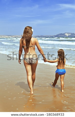 A woman with a child by the hand goes along the sea shore