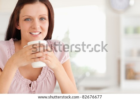 A woman with a cup of coffee is looking at the camera
