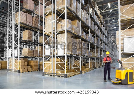A worker in a huge distribution warehouse with high shelves